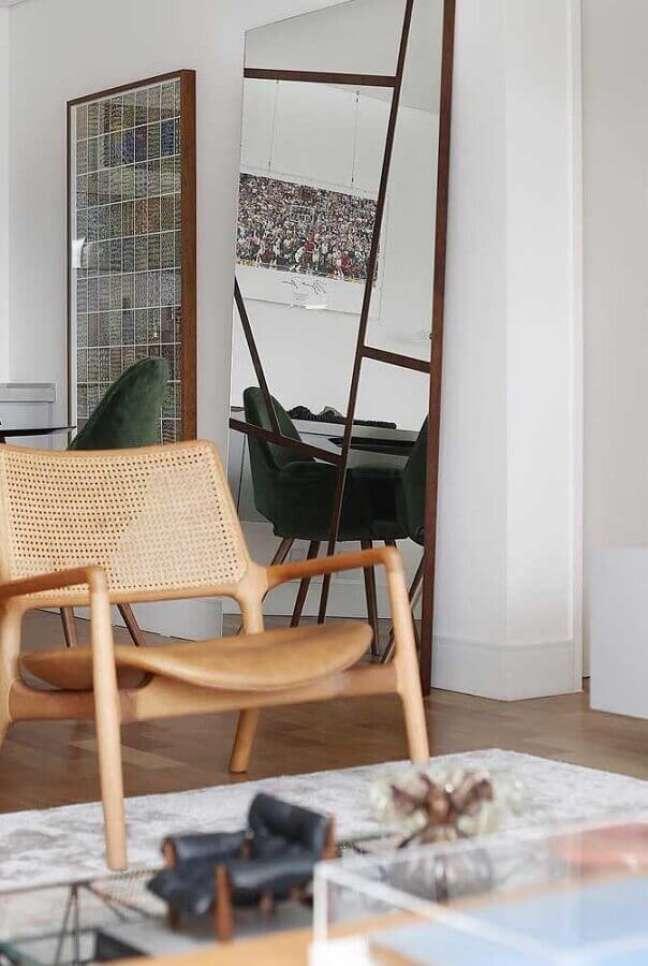 18. Decoração com espelho na sala de estar com poltrona de madeira – Foto: Decor Fácil
