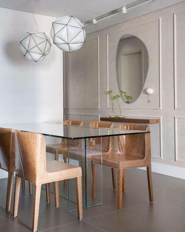 54. Modelo diferente de espelho na sala de jantar decorada com mesa de vidro e cadeiras de couro – Foto: FPR Studio