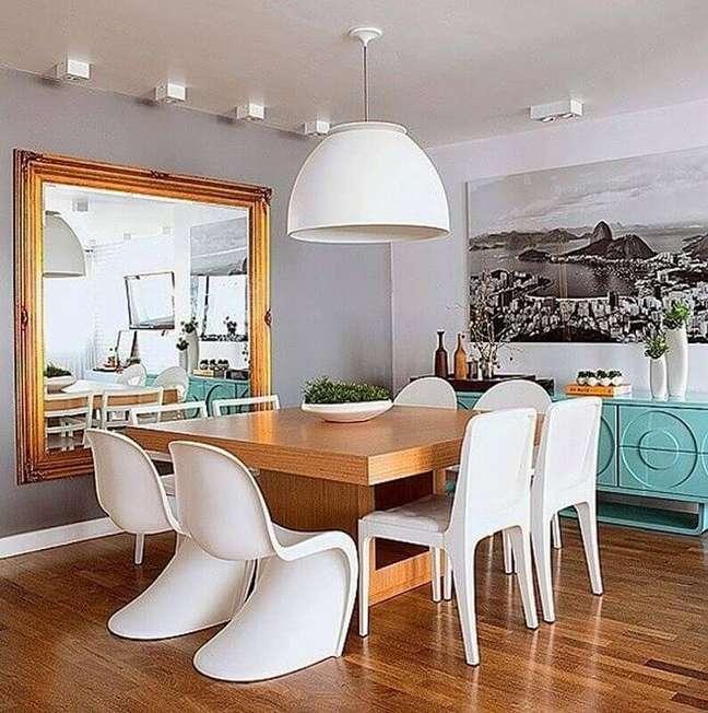 5. Espelho na sala de jantar cinza decorada com buffet azul e mesa quadrada de madeira – Foto: Houzz