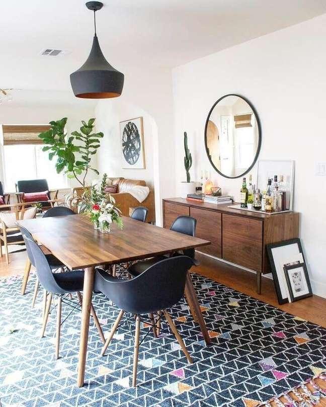 53. Espelho redondo na sala de jantar decorada com tapete preto e buffet de madeira – Foto: LIV Decora