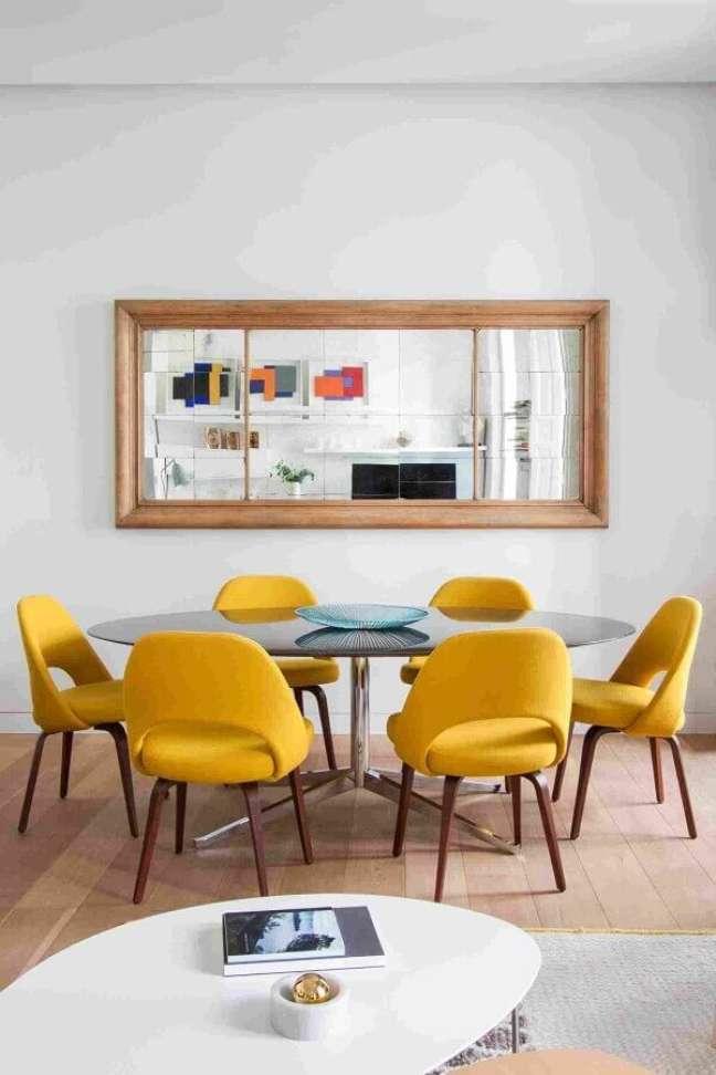 55. Parede com espelho na sala de jantar decorada com cadeira estofada amarela – Foto: Elle Decor