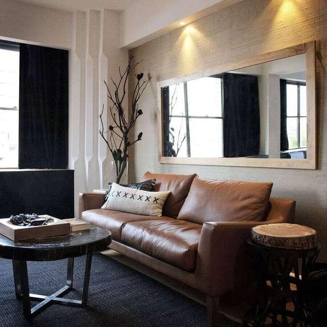 37. Espelho na sala de estar decorada com tapete preto e sofá de couro – Foto: Houzz