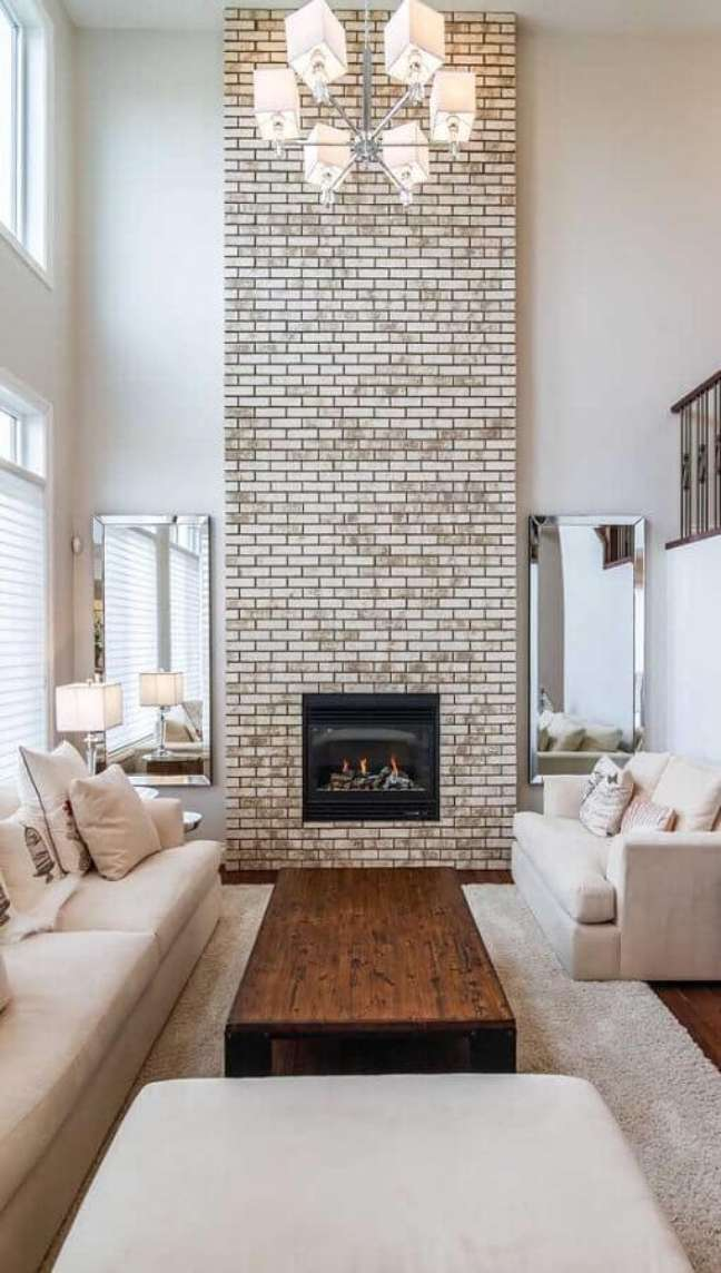10. Cores neutras para decoração com espelho na sala de estar com lareira – Foto: Apartment Therapy