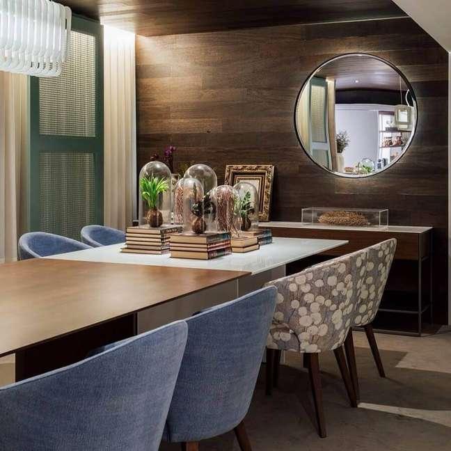 19. Decoração com espelho na sala de jantar com parede amadeirada e cadeiras estofadas – Foto: Hadra Mobiliario