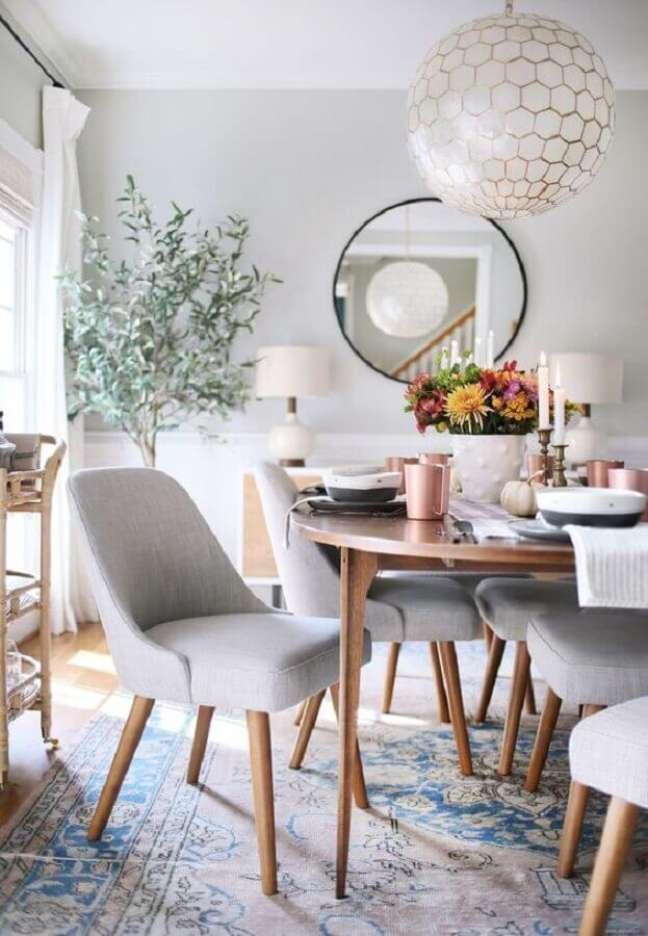20. Decoração com lustre e espelho redondo na sala de jantar clean – Foto: Sunny Circle Studio