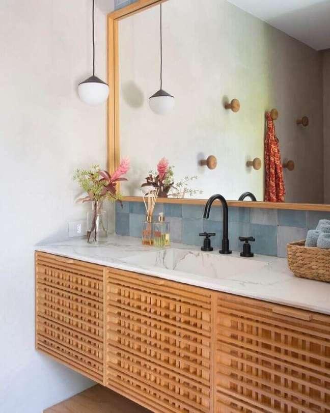 7. Gabinete de madeira com bancada de mármore para decoração de banheiro simples e bonito – Foto: Migs Arquitetura