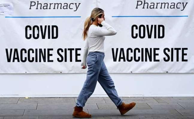 Pedestres caminham do lado de fora de centro de vacinação anti-Covid em Londres, Reino Unido