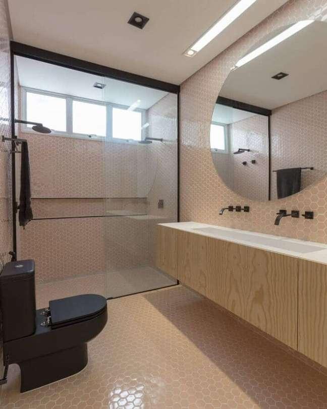 60. Revestimento hexagonal rosa para decoração de banheiro bonito com gabinete suspenso de madeira – Foto: WF Arquitetos