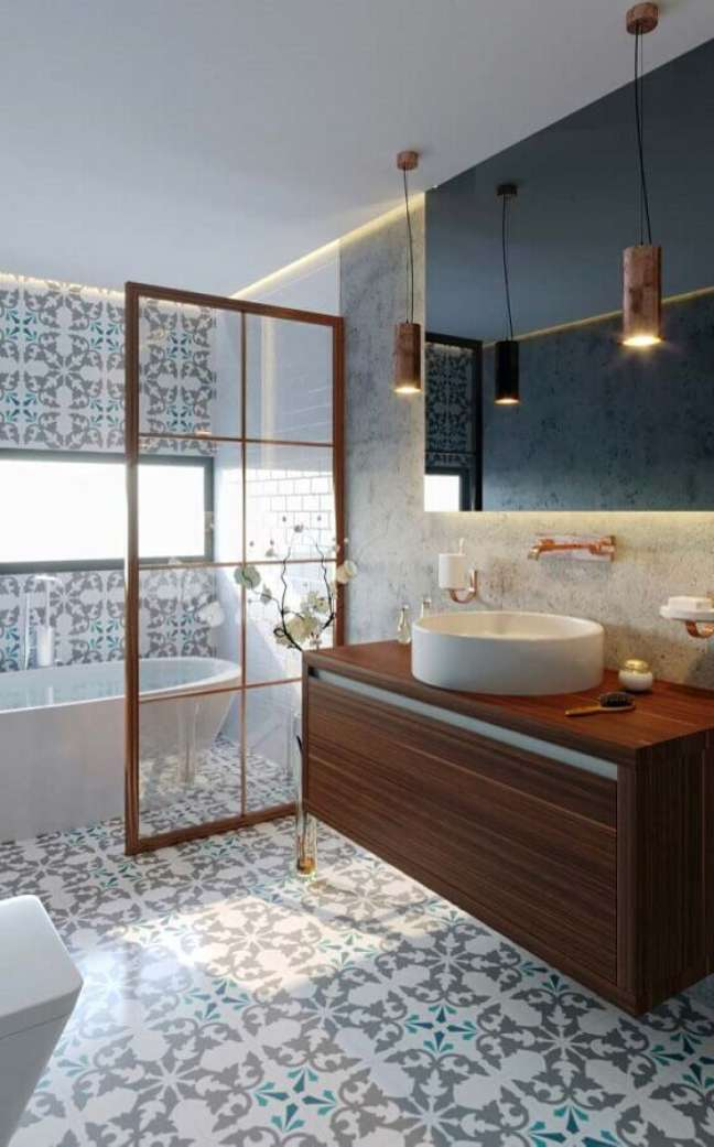 51. Piso estampado para banheiro bonito decorado com gabinete de madeira suspenso e banheira – Foto: Arkpad