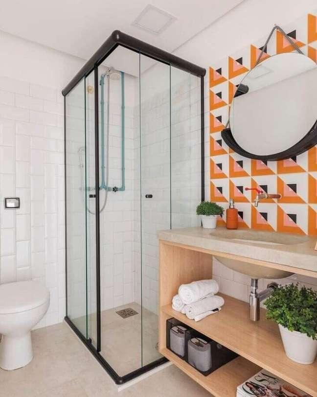 14. Banheiro simples e bonito decorado com revestimento colorido e espelho redondo – Foto: SP Estúdio