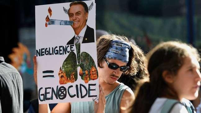 Em Londres, ativista segura cartaz com foto de Bolsonaro e de florestas em chamas, com as palavras 'negligência' e 'genocídio' em inglês
