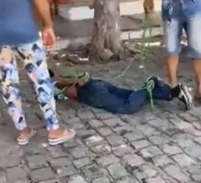 Imagem mostra homem amarrado quando foi agredido no chão