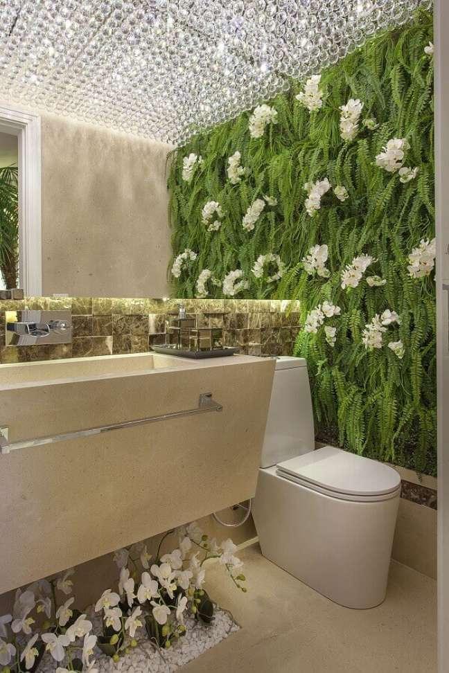 41. Lustre de cristal para banheiro bonito de luxo decorado com jardim vertical – Foto: Iara Kilaris