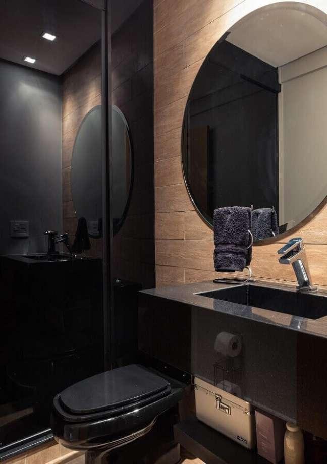 36. Espelho redondo para banheiro bonito preto decorado com revestimento de madeira – Foto: Braccini + Lima Arquitetura