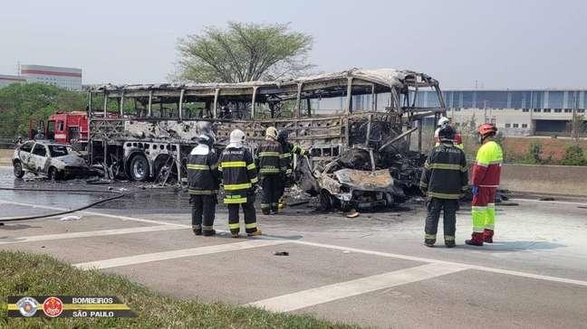 Bombeiros tentam conter incêndio no ônibus, que ficou completamente destruído após o acidente