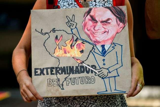 'Exterminador do futuro', diz cartaz que mostra Bolsonaro com um palito de fósforo, incendiando a Amazônia. Cali (Colômbia), agosto de 2019