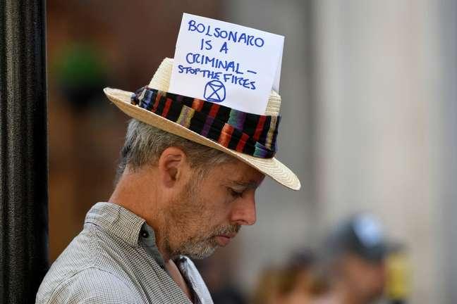 'Bolsonaro é um criminoso — Parem os incêndios', diz mensagem no chapéu de ativista em protesto na Embaixada do Brasil em Londres, em 2019