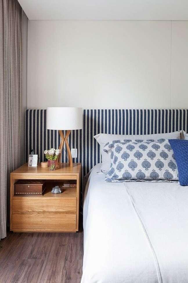 26. Cama com cabeceira almofadada listrada para quarto branco decorado com criado mudo de madeira – Foto R. A. P. Arquitetura