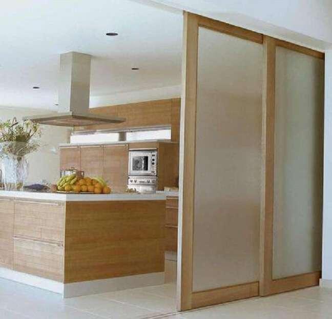 35. Porta de madeira e vidro para sala camufla o ambiente da cozinha. Fonte: Arkpad