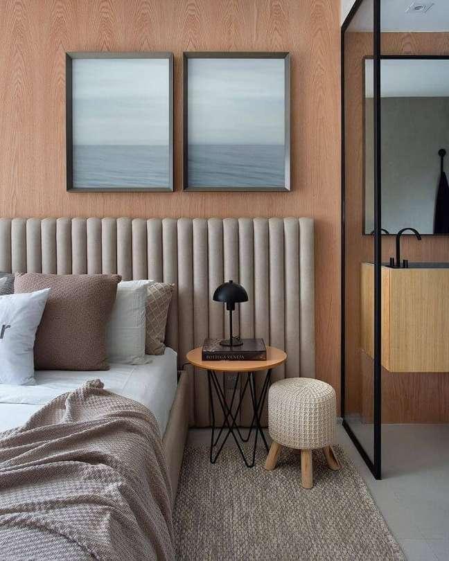 15. Cabeceira almofadada moderna para quarto de casal decorado com parede de madeira – Foto: Carlos Carvalho