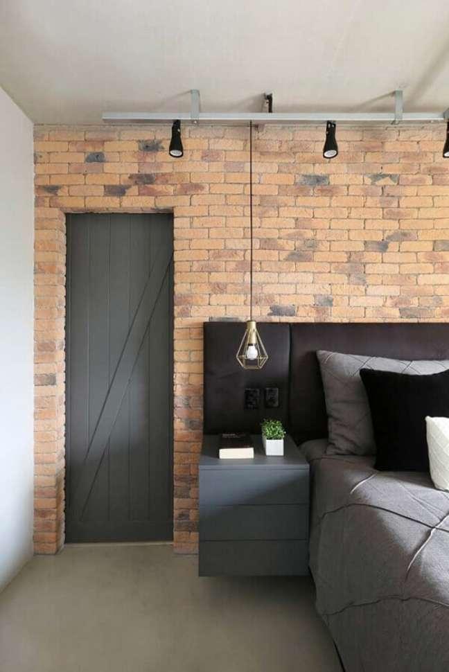 7. Cabeceira almofadada com criado mudo para quarto decorado com parede tijolinho e luminária pendente – Foto: SP Estúdio