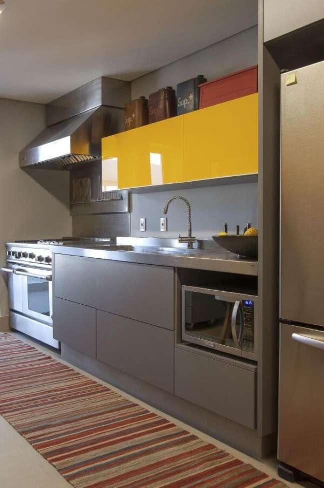 9. Cozinha com bancada e eletrodomésticos cor prata de inox e armário amarelo – Foto Antonio Ferreira Junior e Mario Celso Bernardes