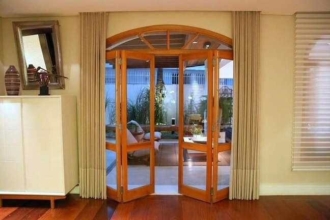 17. A porta de vidro para sala simples feita com acabamento em madeira dá acesso à varanda. Fonte: Meyer Cortez