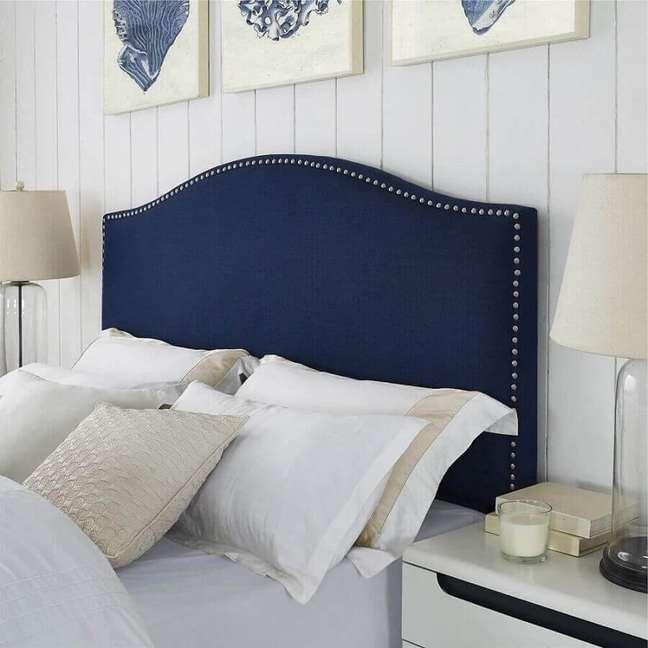 34. Decoração de quarto branco com cabeceira almofadada azul marinho com tachas – Foto: Gameol