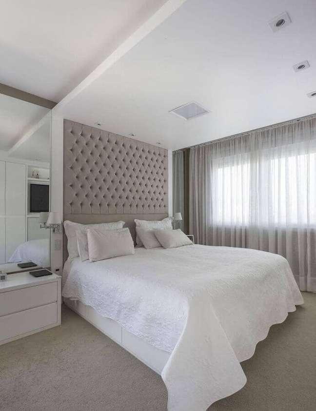 51. Quarto branco grande decorado com cabeceira almofadada planejada ate o teto – Foto: Kali Arquitetura