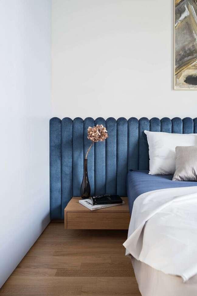 4. Cama com cabeceira almofadada azul planejada para decoração de quarto branco com criado mudo suspenso de madeira – Foto: Dwell