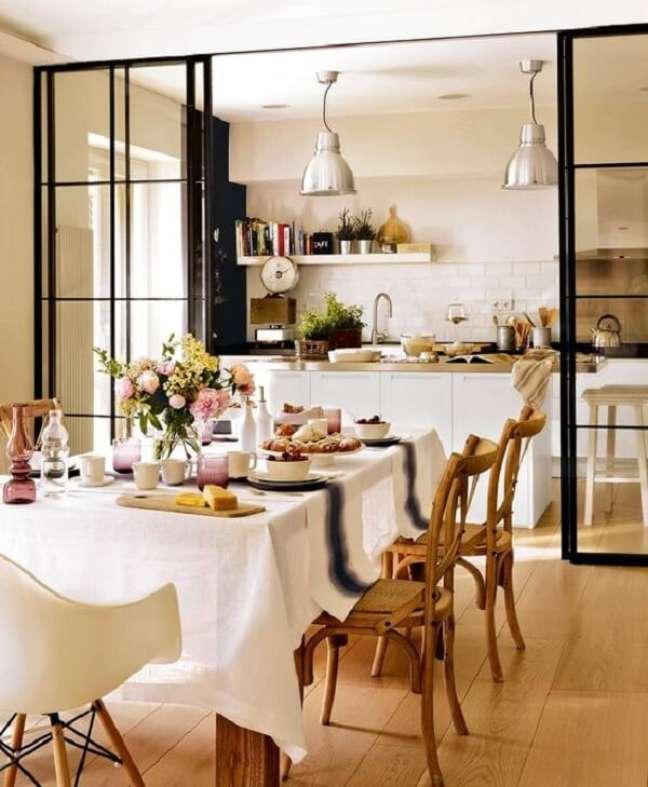 21. Cozinha integrada com sala de estar dividida por porta de correr de vidro. Fonte: El Mueble