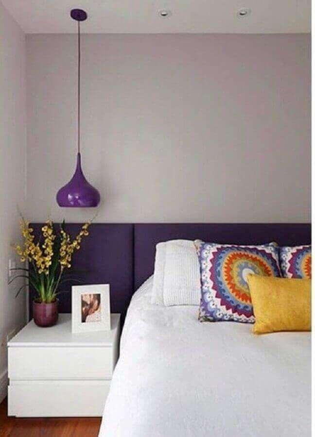 27. Cama com cabeceira almofadada para decoração de quarto de casal com luminária roxa – Foto: Deu Decor
