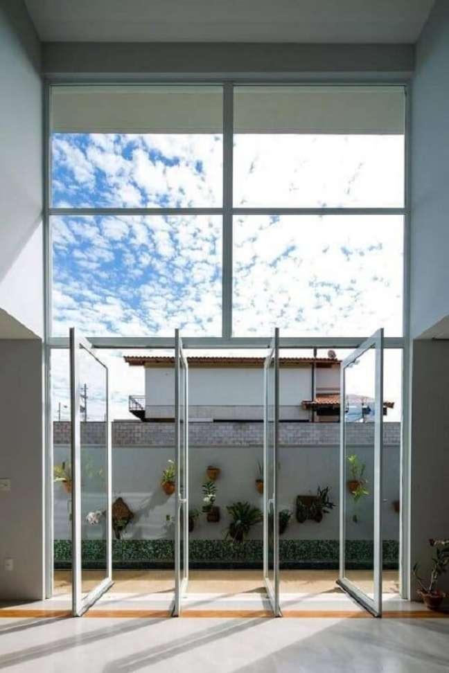 46. Porta para sala de vidro do tipo pivotante favorece a entrada de luz natural e ventilação no ambiente. Fonte: JAA Arquitetos