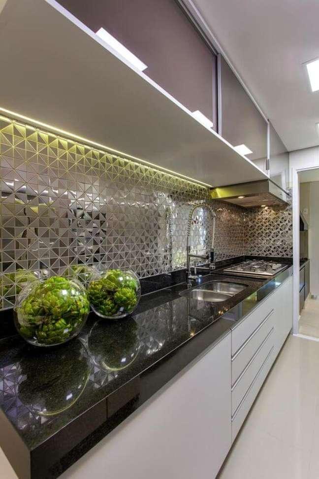 1. Cozinha com revestimento cor prata e bancada preta – Foto Iara Kilaris