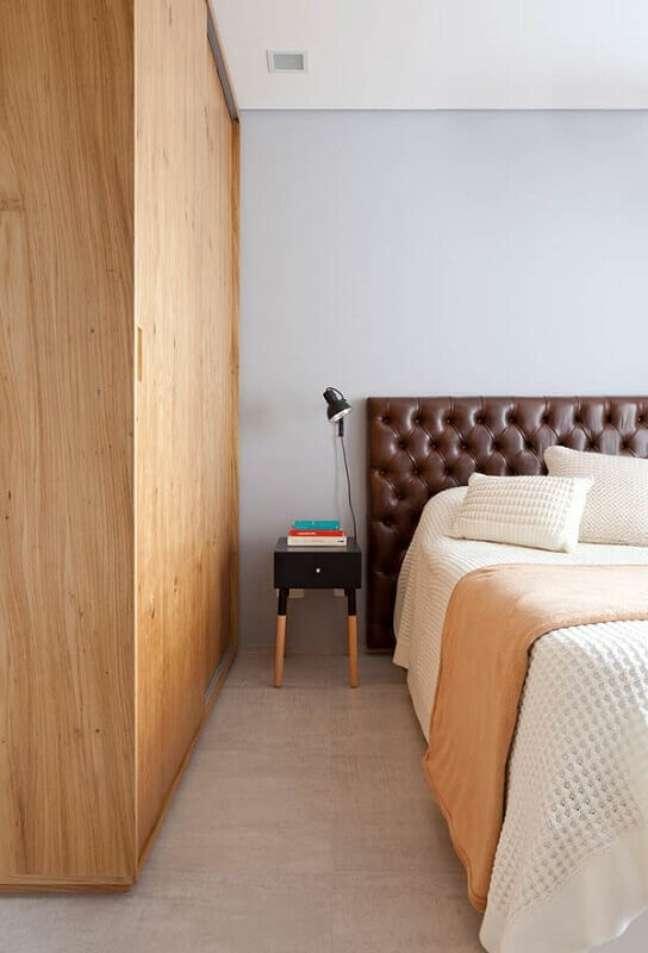 22. Cama com cabeceira almofadada casal de couro para quarto decorado com guarda roupa de madeira – Foto: Escritório Metamoorfose