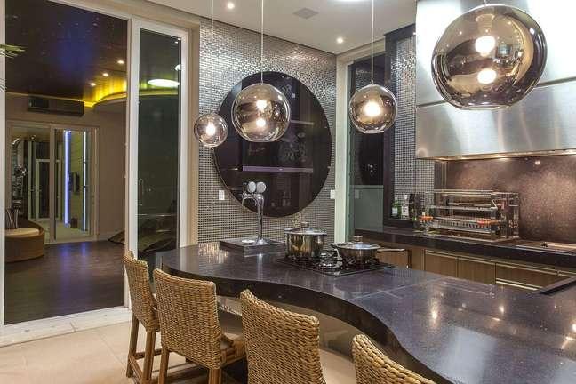 51. Balcão de cozinha iluminado com lustre na cor prata e revestimento de pastilha na mesma cor – Foto Iara Kilaris