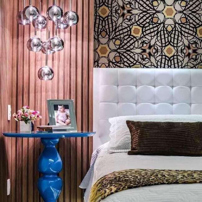 2. Cama com cabeceira almofadada branca para decoração de quarto com mesa lateral azul – Foto: Carla Sampaio