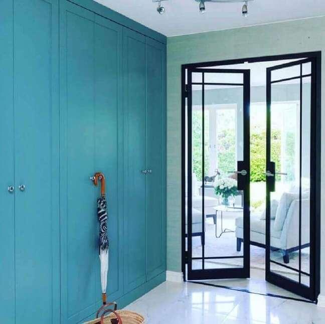 37. Porta de vidro com ferro para sala e armário embutido pintado de azul. Fonte: Metal Form