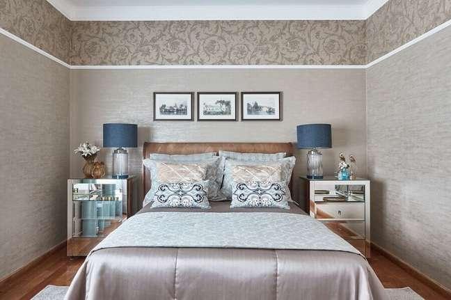 11. Cabeceira almofadada casal para quarto decorado com criado mudo espelhado e papel de parede com arabescos – Foto: Piloni Arquitetura