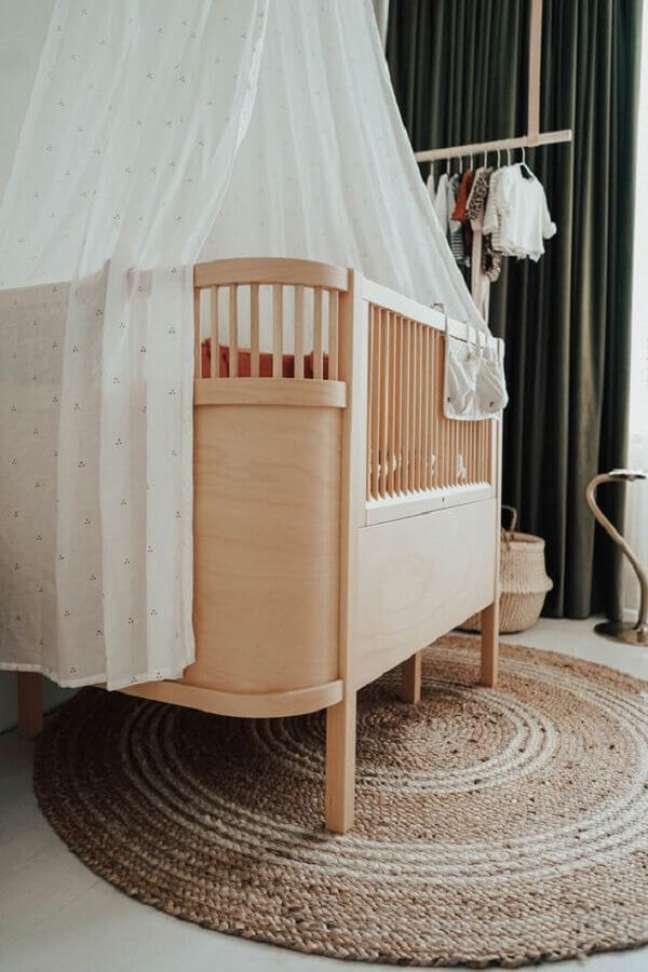 14. Berço de bebê de madeira para decoração de quarto com tapete redondo rustico – Foto: fonQ