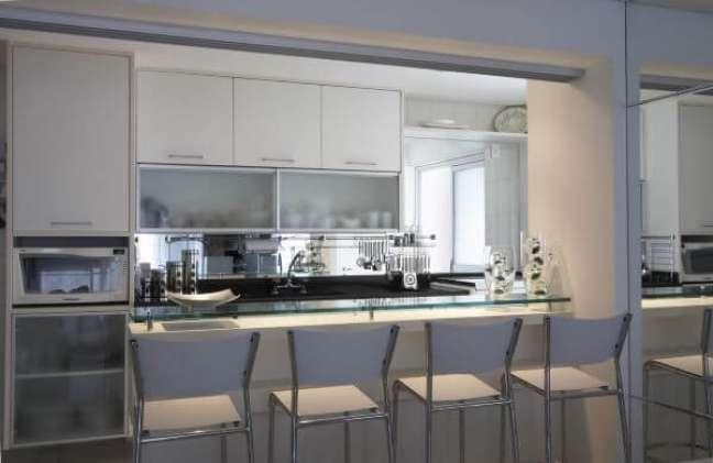 38. Cozinha com armário de vidro para copos e pratos organizados – Foto Leoshehtman