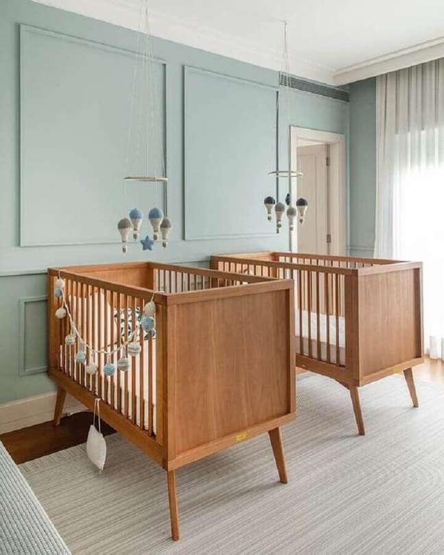 16. Berço de bebê de madeira para quarto de gêmeos decorado com parede azul claro – Foto: Triplex Arquitetura
