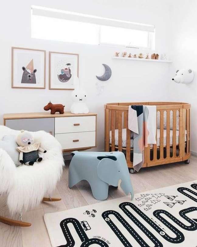 53. Quarto de bebê branco decorado com tapete lúdico e berço de madeira – Foto: Tarina Wood