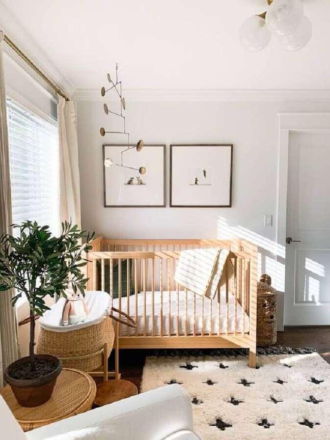 54. Quarto de bebê branco decorado com vaso de planta e berço de madeira simples – Foto: Elizabeth Street Post