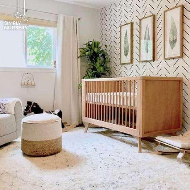 9. Berço cor de madeira para quarto branco decorado com vaso de planta e puff redondo – Foto: Simply Nursery