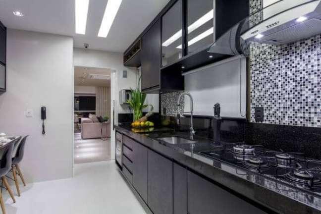 51. Cozinha preta planejada com armário de vidro – Foto Vanja Maia