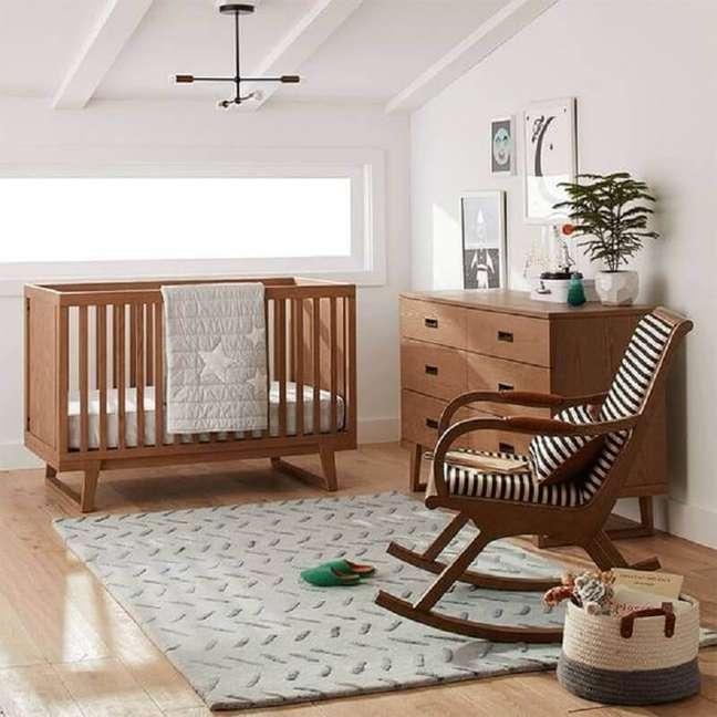 57. Quarto de bebê simples decorado com cadeira de balanço e berço de madeira – Foto: Crate and Barrel