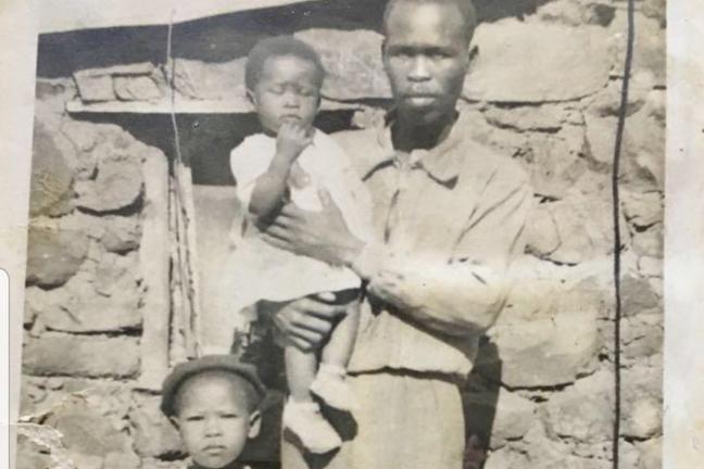 Agnes e seu pai, com sua irmã mais nova no colo, em frente à casa onde ela nasceu