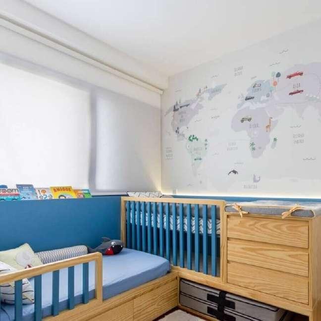 11. Berço de madeira com gaveta e trocador para quarto de bebê azul e branco decorado com mapa na parede – Foto: UEBAA