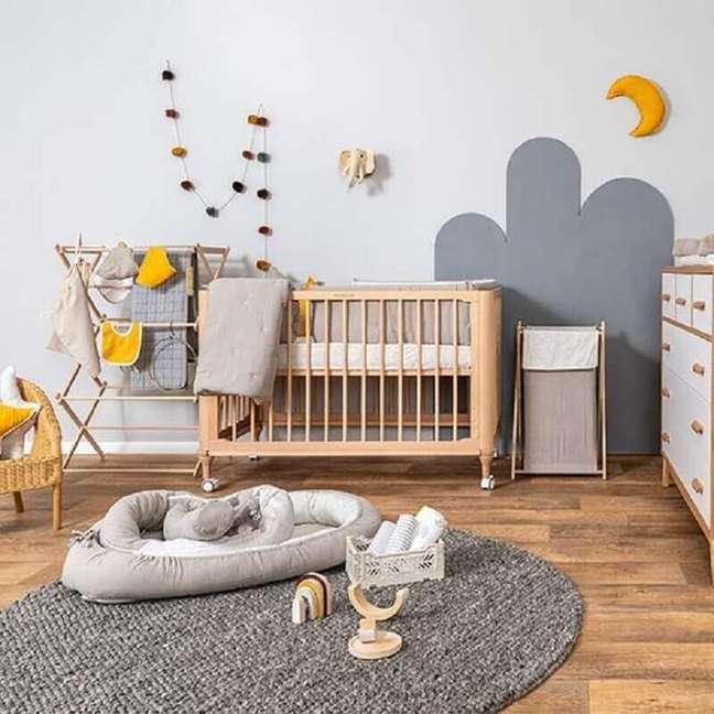 18. Berço de bebê de madeira para quarto simples decorado com tapete redondo cinza – Foto: Baby Bedding Design